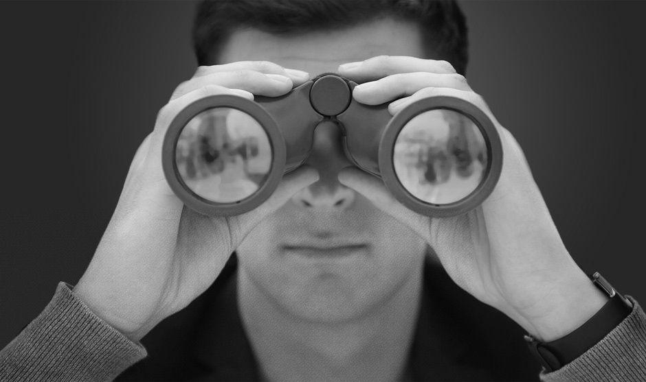 Detective vigilando con binocular