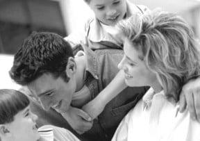 Un matrimonio con sus hijos abrazados felizmente