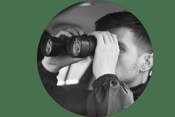 Un detective vigilando con binoculares desde el interior de un vehículo