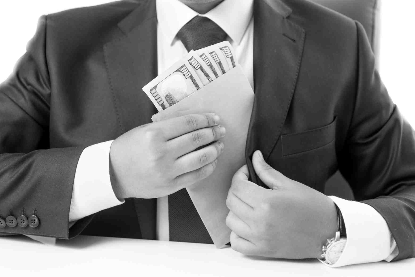 Individuo con traje guarda un sobre con dinero